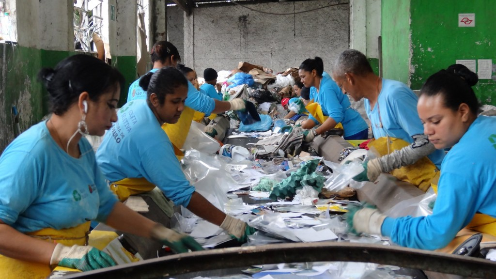 Homens e mulheres na esteira de triagem de materiais recicláveis em uma cooperativa. Foto: Lusimar Pereira.