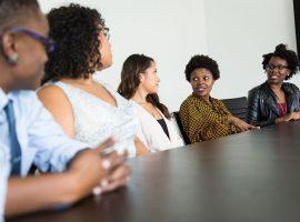Foto de quatro mulheres e um homem reunidos em uma sala fechada. Há uma mesa grande e eles estão sentados em volta dela.