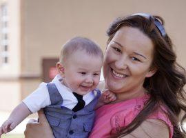 Foto de uma mulher segurando seu filho no colo.