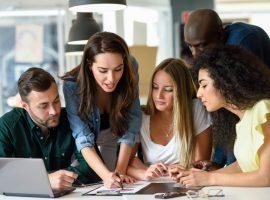 Foto de um grupo de jovens funcionários, dois homens e três mulheres, trabalhando. Eles olham para um documento em cima de uma mesa