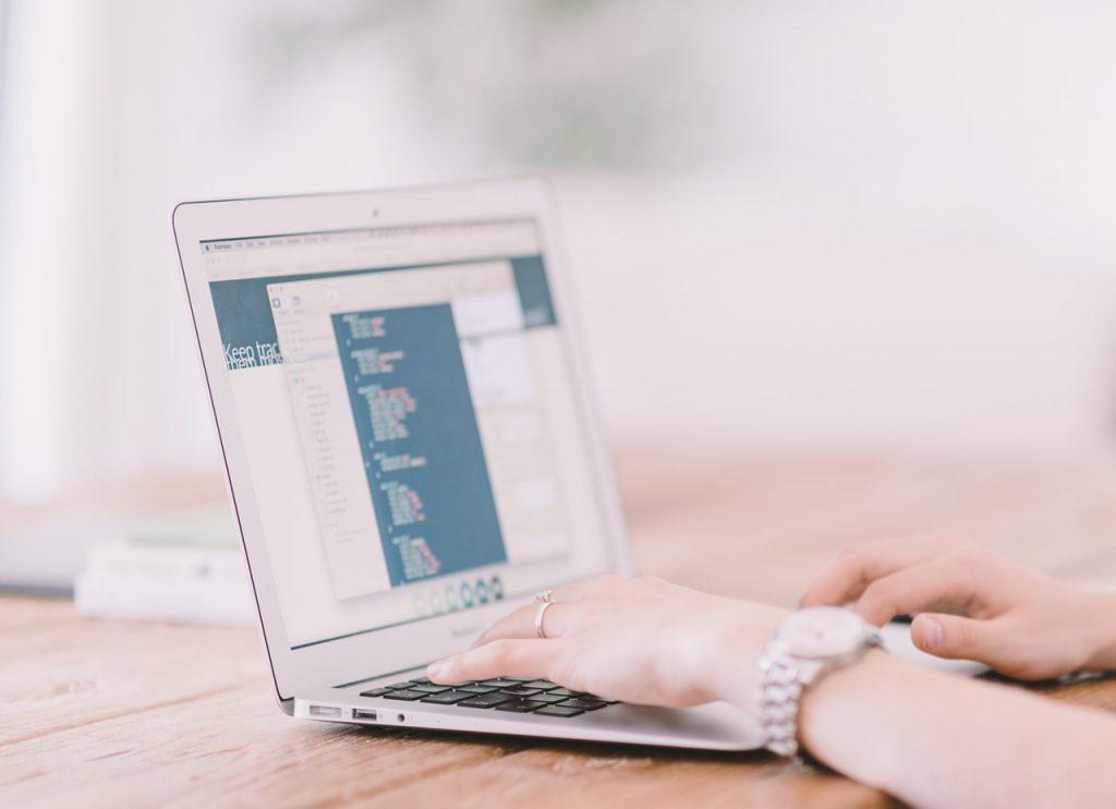 Foto de mãos femininas no teclado de um laptop em cima de uma mesa.
