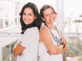 Foto da Susana e da Luciana com os braços cruzados, sorrindo. Uma está de costas para a outra.