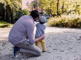 Foto de um homem ajoelhado ao lado de uma criança em pé. Ele apoia uma das mãos na criança e olha para a mesma direção que ela.