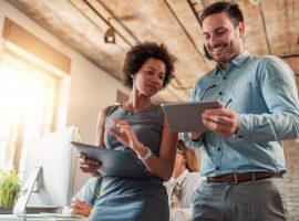 Foto de uma mulher e um homem, ambos seguram nas mãos um tablet. Ela está olhando para a tela do aparelho que ele está segurando.