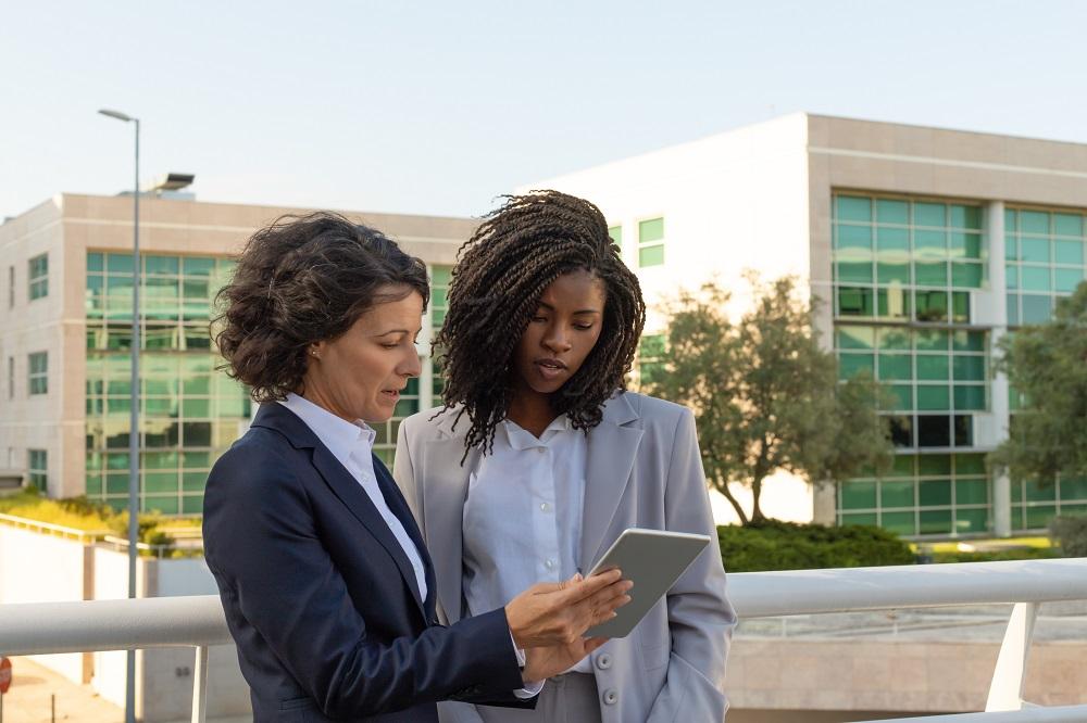 Foto de duas executivas em um local aberto. Elas estão próximas e olham para um tablet que está sendo segurado por uma delas.