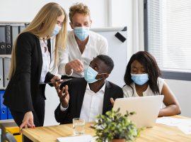 Foto de duas mulheres e dois homens em um escritório. Todos estão usando máscara de proteção cobrindo o nariz e a boca.