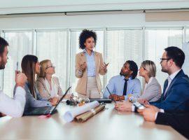 Foto de um grupo diverso de homens e mulheres em um escritório. Um mulher está em pé, no centro, enquanto os demais estão sentados ao redor de uma mesa.