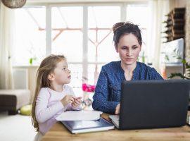 Foto de uma mulher sentada na sala de sua casa. Ela está trabalhando com um laptop e ao seu lado está sua filha.