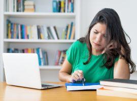 Foto de uma mulher sentada em uma cadeira. Ela está com a mão direita encostada no rosto enquanto a esquerda segura uma caneta. Em cima da mesa há um laptop e alguns livros.