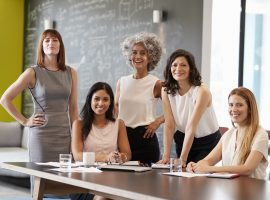 Foto de cinco mulheres em uma sala de reunião