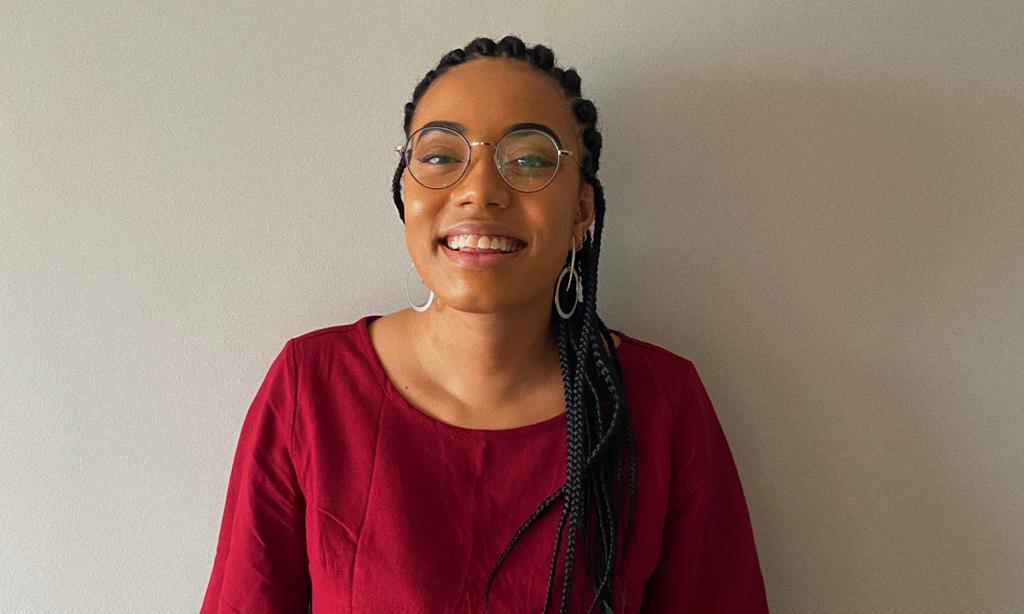 Foto de Laís Souza encostada em uma parede. Ela usa óculos, está sorrindo e seus cabelos estão com várias tranças.