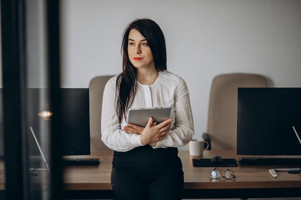 Foto de uma mulher em um escritório. Ela está em pé e segura um tablet nas mãos
