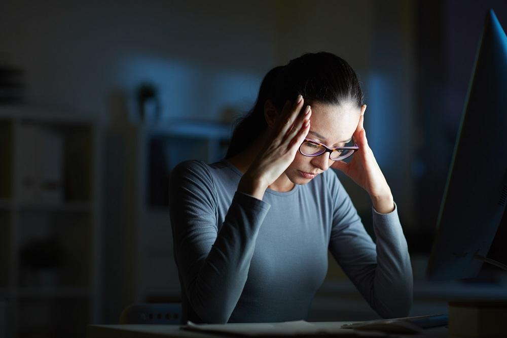Foto de uma mulher sentada em uma sala escura