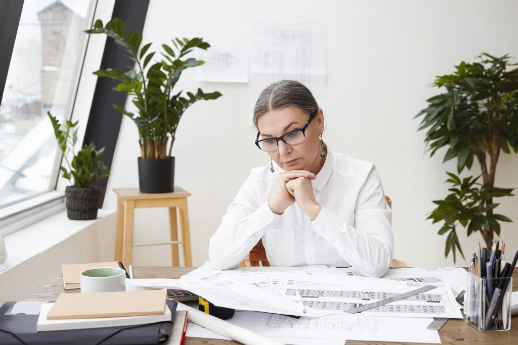 Foto de uma mulher com as mãos apoiadas embaixo do queixo. Ela olha para uma pilha de papeis que estão em cima de uma mesa.