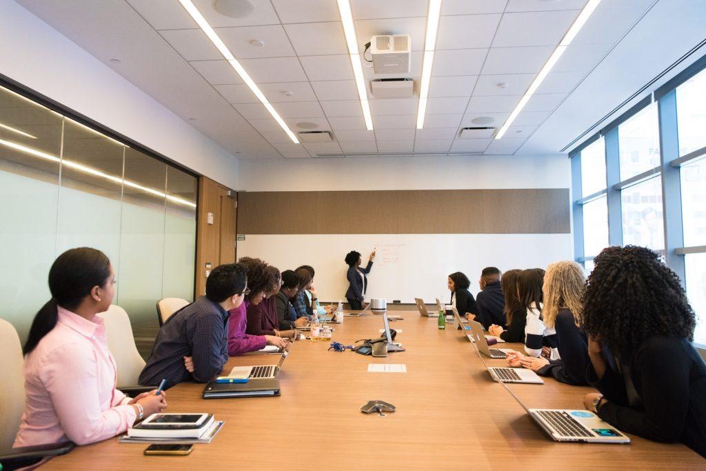 Foto de um grupo diverso de pessoas reunidas em uma sala de reuniões. No centro, há uma mulher em pé fazendo uma apresentação.