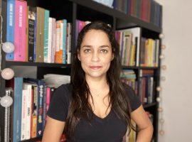 Foto posada de Ana Tomazelli em pé em frente a uma estante de livros