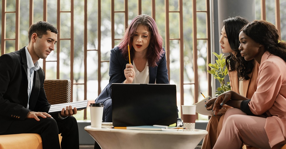 Foto de três mulheres e um homem reunidos ao redor de uma mesa de centro em um escritório