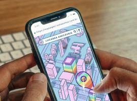 Foto de mãos masculinas segurando um celular com a página do Mapa LGBTI aberta