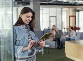 Foto de uma mulher grávida, em pé, com um tablet nas mãos