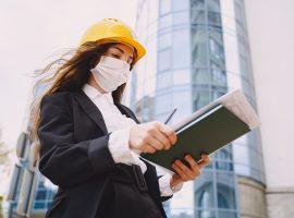 Foto de uma mulher jovem, em frente a um prédio, com capacete e máscara cobrindo a boca e o nariz