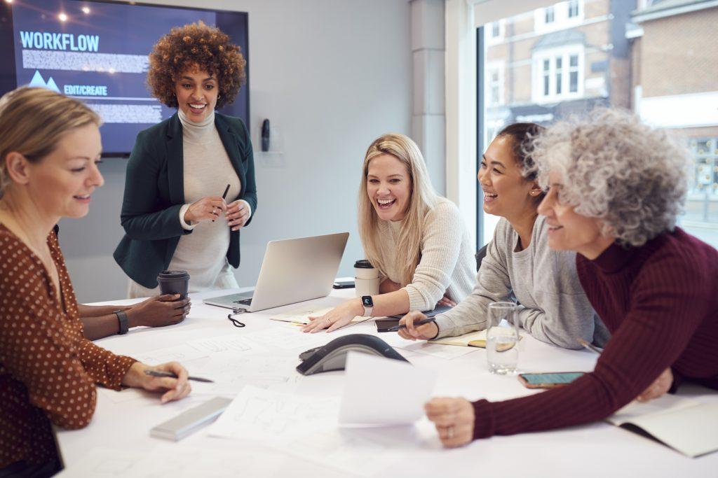 Foto de cinco mulheres ao redor de uma mesa de reuniões em uma sala