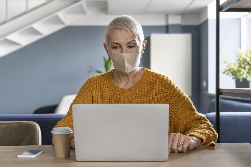Foto de uma mulher idosa, de cabelos curtos, usando máscara, enquanto usa um laptop