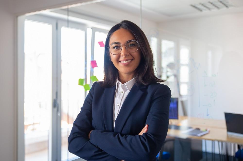 Foto de uma mulher jovem com os braços cruzados em um escritório