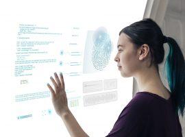 Foto de uma jovem em frente a uma tela com várias linhas de código e uma digital gigante, ela toca na tela com a mão esquerda.