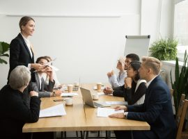 Foto de uma sala de reunião em que uma mulher está em pé, em destaque, e o restante da equipe está sentada