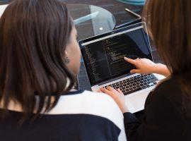 Foto de duas mulheres negras sentadas lado a lado, e uma delas aponta com o dedo indicador da mão direita para a tela de um laptop com vários códigos de programação