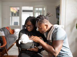 Foto de uma mulher com um bebê no colo, e ao seu lado há um homem com a mão esquerda na criança