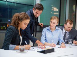 Foto de duas mulheres e um homem sentados à mesa de um escritório, e entre elas, há mais um homem, este está em pé, e indica com a mão esquerda algo em um papel que está sob a mesa.