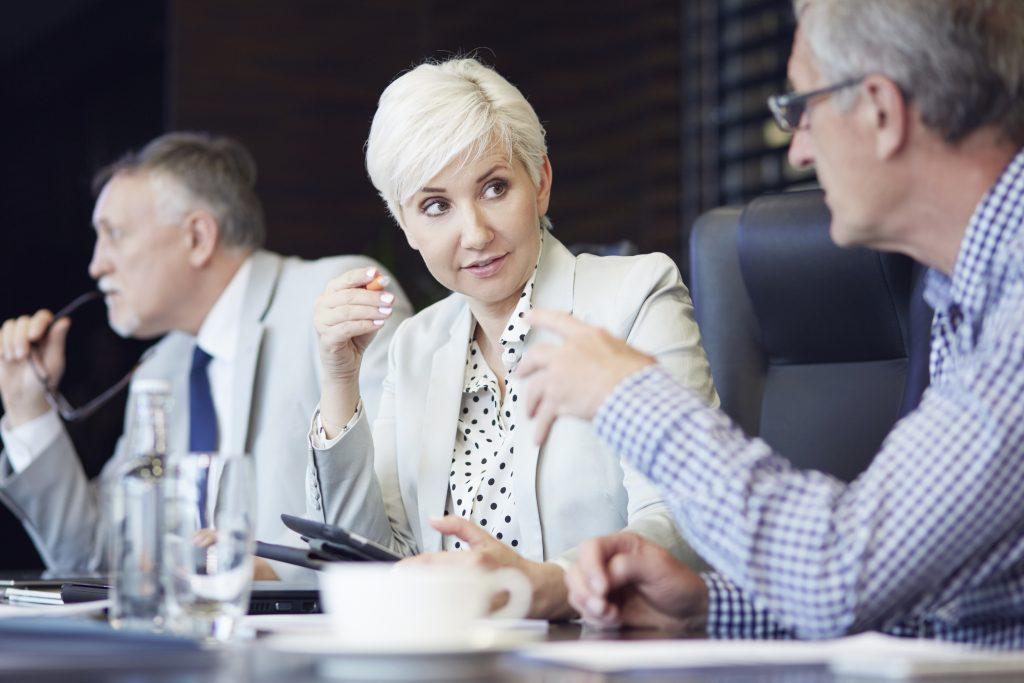 Foto de dois homens e uma mulher sentados em uma mesa de reuniões conversando