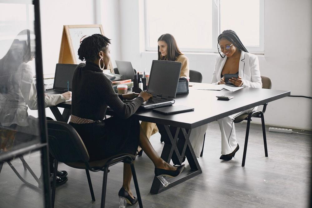 Foto de quatro mulheres sentadas e compartilhando a mesma mesa em um escritório. Há laptops e papéis sobre a mesa.