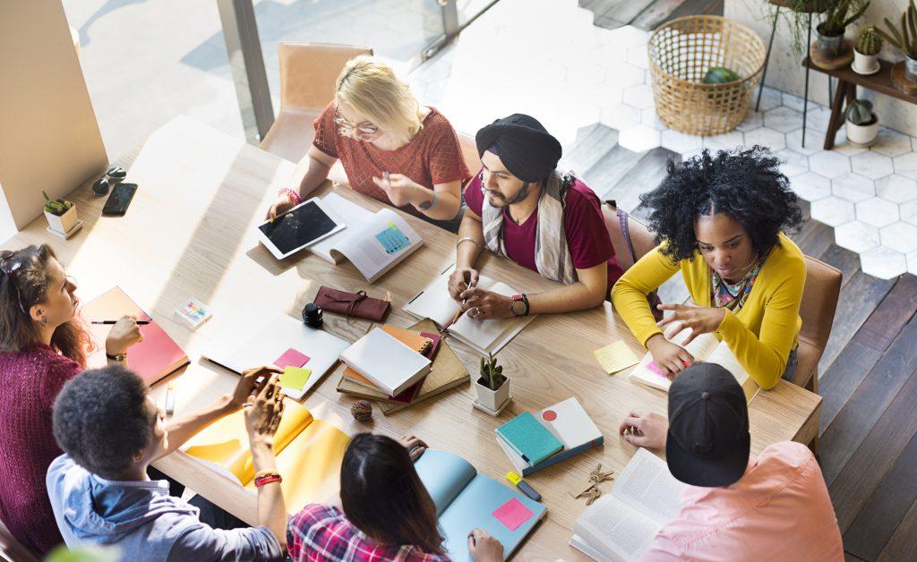 Foto de um grupo de sete pessoas diversas sentadas ao redor de uma mesa, em um escritório bem iluminado, conversando. Sobre a mesa há tablets, cadernos, post-its, celulares, marca textos e itens pessoais.