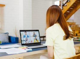 Foto de uma jovem mulher de costas sentada em frente a um computador que está com uma chamada de vídeo na tela com quatro pessoas