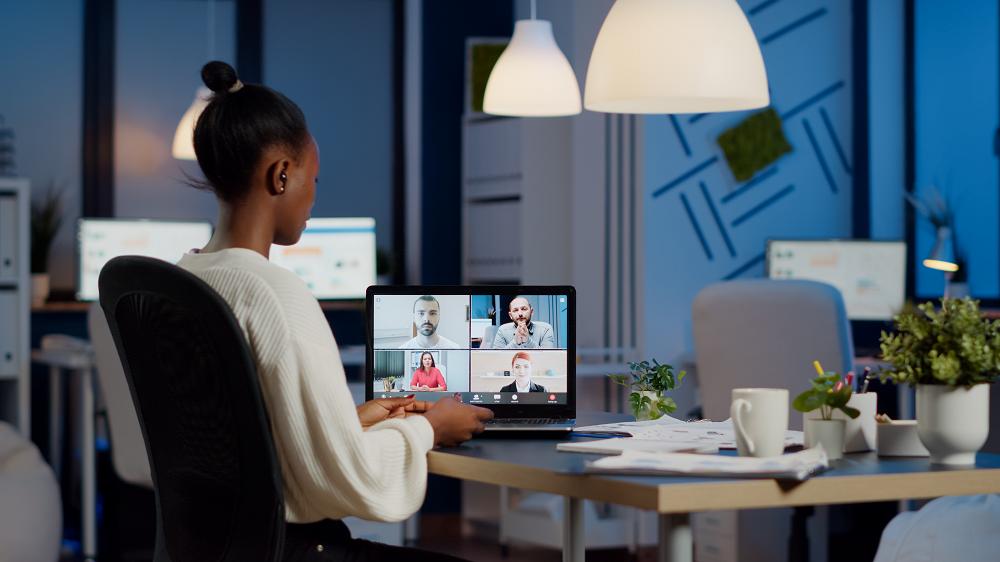 Foto de uma mulher negra sentada, em uma sala, e na sua frente há uma mesa e sobre ela um computador. Na tela, há uma chamada de vídeo em andamento com a participação de quatro pessoas.