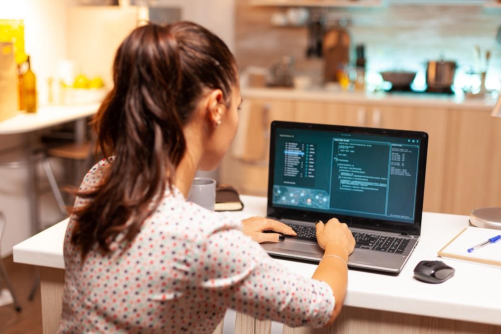Foto de uma mulher sentada à mesa trabalhando em um laptop com uma série de códigos de programação na tela do equipamento